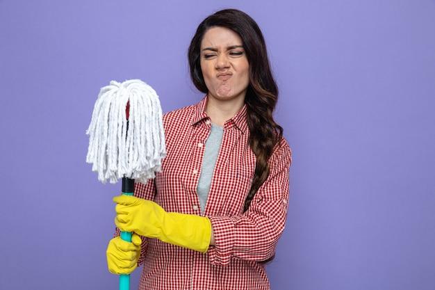 Niezadowolona ładna kaukaska sprzątaczka w gumowych rękawiczkach trzymająca i patrząca na mopa