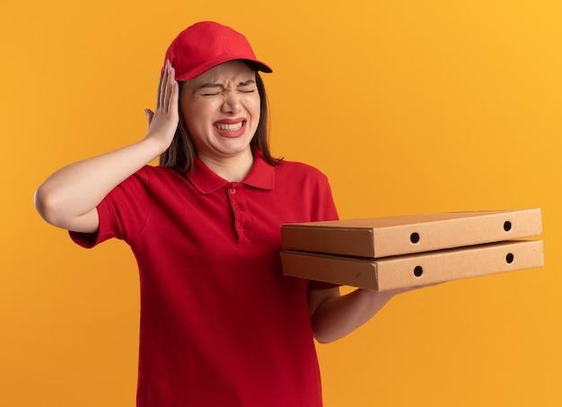 Niezadowolona ładna kobieta doręczycielska w mundurze kładzie rękę na głowie i trzyma pudełka po pizzy na pomarańczowej ścianie z miejscem na kopię