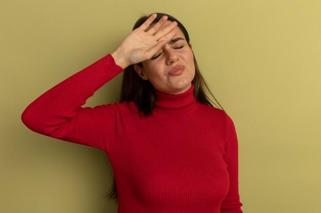 Niezadowolona ładna kobieta kładzie dłoń na czole odizolowane na oliwkowej ścianie