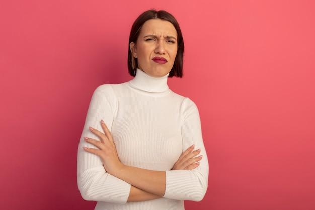 Niezadowolona ładna kobieta stojąca ze skrzyżowanymi rękami na białym tle na różowej ścianie