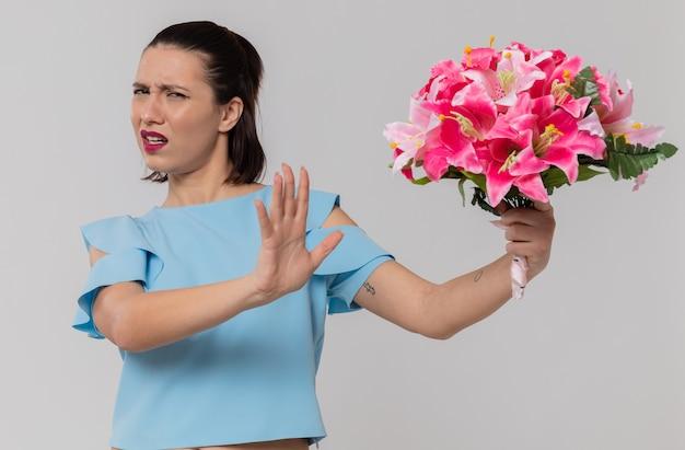 Niezadowolona ładna młoda kobieta trzyma bukiet kwiatów