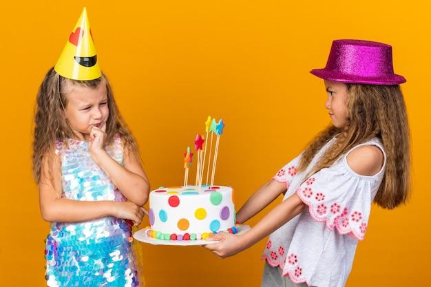 Niezadowolona mała blondynka w imprezowej czapce patrząca na małą kaukaską dziewczynkę w fioletowym kapeluszu trzymającym tort urodzinowy odizolowaną na pomarańczowej ścianie z miejscem na kopię