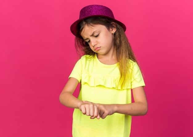 Niezadowolona mała kaukaska dziewczynka w fioletowym kapeluszu imprezowym, patrząca i kładąca palec na dłoni, odizolowana na różowej ścianie z miejscem na kopię