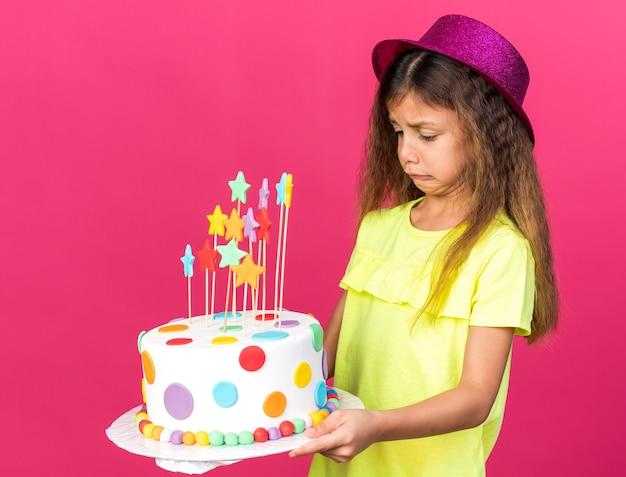 Niezadowolona mała kaukaska dziewczynka w fioletowym kapeluszu imprezowym trzymająca i patrząca na tort urodzinowy odizolowany na różowej ścianie z miejscem na kopię