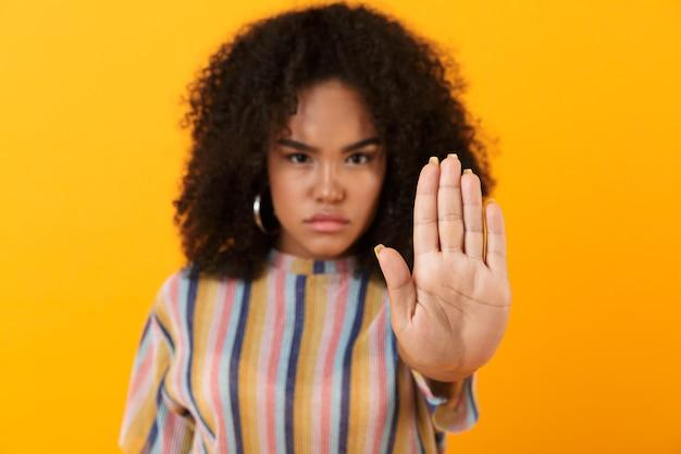 Niezadowolona młoda afrykańska śliczna dziewczyna pozuje na białym tle nad żółtą przestrzenią, wykonując gest stopu.
