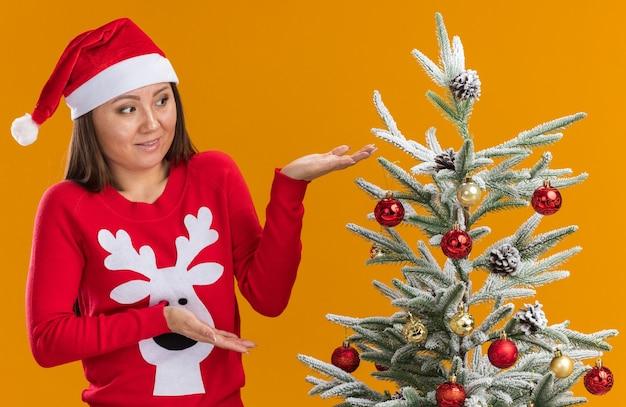 Niezadowolona młoda azjatycka dziewczyna ubrana w świąteczny kapelusz ze swetrem stojąca w pobliżu choinki na pomarańczowej ścianie