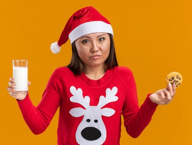 Niezadowolona młoda azjatycka dziewczyna w świątecznym kapeluszu ze swetrem trzyma szklankę mleka z ciasteczkami na białym tle na pomarańczowej ścianie