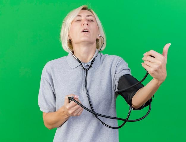 Niezadowolona młoda blond chora słowiańska kobieta stoi z zamkniętymi oczami mierząc ciśnienie