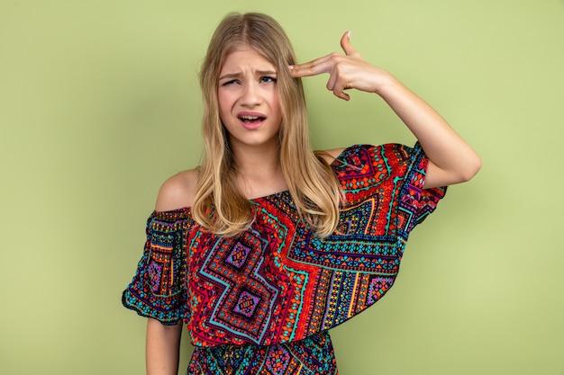 Niezadowolona młoda blond słowiańska dziewczyna trzyma rękę na swojej skroni, gestykulując znak pistoletu