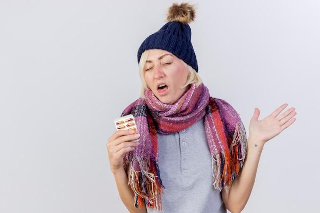 Niezadowolona młoda blondynka chora kobieta w czapce zimowej i szaliku stoi z podniesioną ręką i trzyma opakowanie tabletek medycznych na białej ścianie