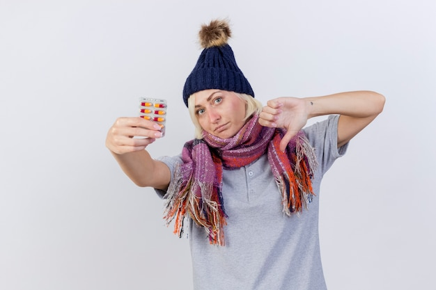 Niezadowolona młoda blondynka chora słowiańska kobieta w czapce zimowej i szaliku z kciukami w dół i trzyma paczkę tabletek medycznych na białej ścianie z miejscem na kopię
