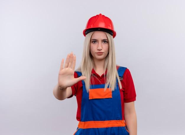 Niezadowolona młoda blondynka inżynier konstruktor dziewczyna w mundurze wyciągająca rękę, wskazująca nie na odosobnioną białą ścianę z miejscem na kopię