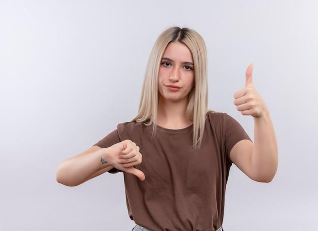 Niezadowolona młoda blondynka pokazuje kciuki w górę iw dół na odosobnionej białej ścianie