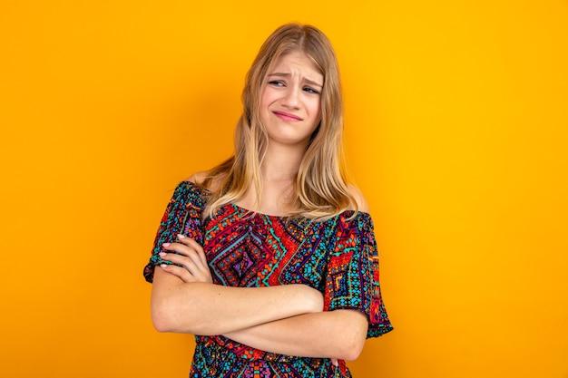 Niezadowolona młoda blondynka stojąca ze skrzyżowanymi rękami i patrząca w bok