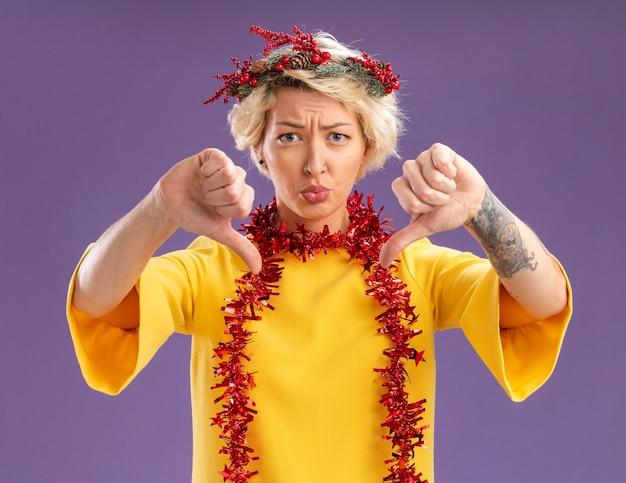 Niezadowolona młoda blondynka ubrana w świąteczny wieniec na głowę i świecącą girlandę na szyi patrząc na kamerę pokazującą kciuki w dół na białym tle na fioletowym tle