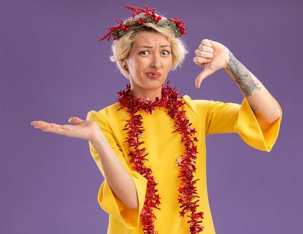 Niezadowolona młoda blondynka ubrana w świąteczny wieniec na głowę i świecącą girlandę na szyi patrząc na kamerę pokazującą pustą dłoń i kciuk w dół na białym tle na fioletowym tle