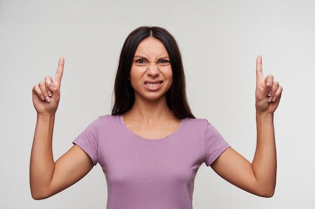 Niezadowolona młoda brązowooka brunetka kobieta z naturalnym makijażem patrząc na kamery z dąsaniem się i marszczącą brwi, pozująca na białym tle z uniesionymi palcami wskazującymi