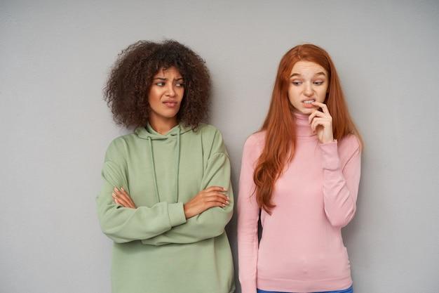 Niezadowolona młoda brązowowłosa ciemnoskóra dama składająca ręce na piersi, patrząc z nadąsaną twarzą na swoją zdezorientowaną, długowłosą rudowłosą przyjaciółkę, stojącą przy szarej ścianie