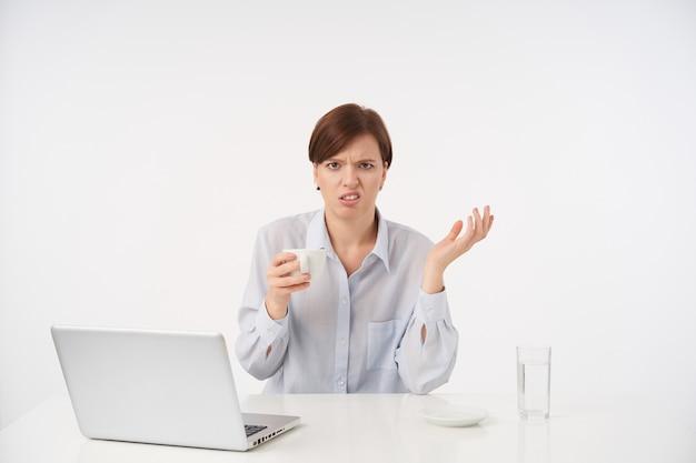 Niezadowolona młoda brązowowłosa kobieta z naturalnym makijażem trzymająca filiżankę kawy i unosząca zdezorientowaną dłoń, marszcząc brwi, odizolowana na białym