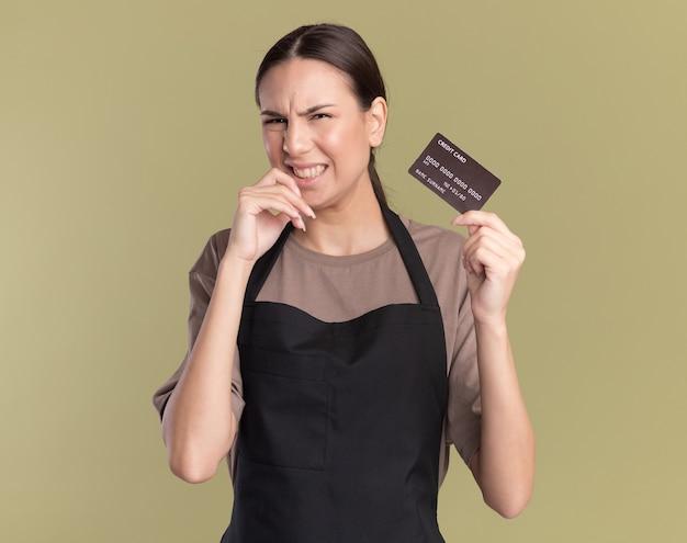Niezadowolona młoda brunetka fryzjerka w mundurze kładzie rękę na brodzie i trzyma kartę kredytową