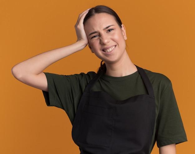 Niezadowolona młoda brunetka fryzjerka w mundurze kładzie rękę na głowie i patrzy na aparat na pomarańczowo