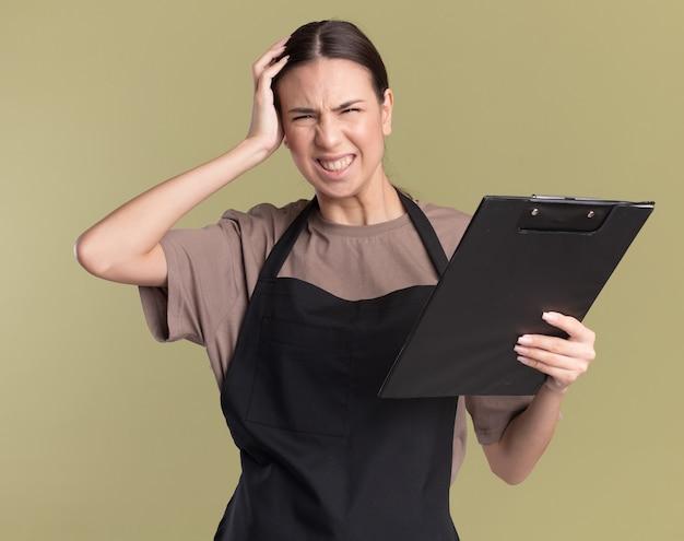 Niezadowolona młoda brunetka fryzjerka w mundurze kładzie rękę na głowie i trzyma schowek