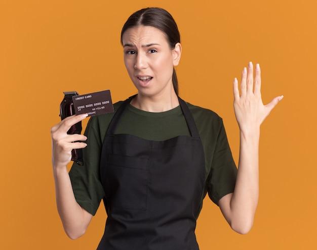 Niezadowolona młoda brunetka fryzjerka w mundurze trzyma rękę otwartą i trzyma maszynkę do strzyżenia włosów z kartą kredytową na pomarańczowo
