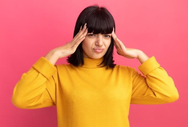 Niezadowolona młoda brunetka kaukaska dziewczyna kładzie ręce na głowie na różowo