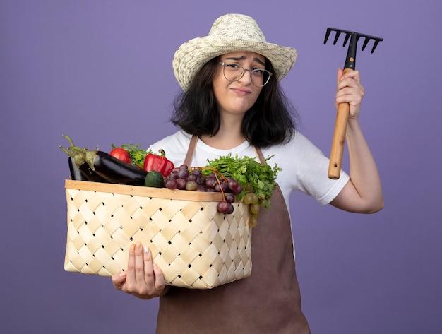 Niezadowolona młoda brunetka ogrodniczka w okularach optycznych i mundurze w kapeluszu ogrodniczym trzyma kosz warzyw i grabie odizolowane na fioletowej ścianie