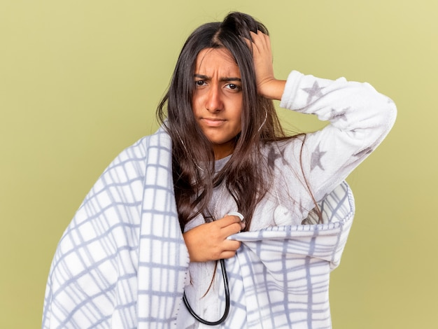 Niezadowolona młoda chora dziewczyna owinięta w kratę nosząca i słuchająca własnego bicia serca ze stetoskopem izolowanym na oliwkowym tle
