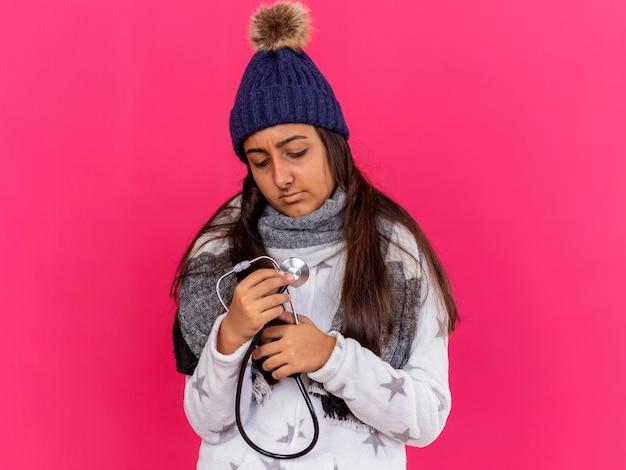 Niezadowolona młoda chora dziewczyna patrząc w dół na sobie czapkę zimową z szalikiem trzymając stetoskop na różowym tle