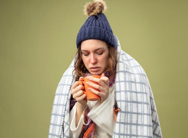 Niezadowolona młoda chora dziewczyna ubrana w białą szatę i czapkę zimową z szalikiem owiniętym w kratę, trzymając i patrząc na filiżankę herbaty odizolowaną na oliwkowej zieleni