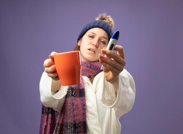 Niezadowolona młoda chora dziewczyna ubrana w białą szatę i czapkę zimową z szalikiem, trzymając filiżankę herbaty z termometrem na fioletowym tle