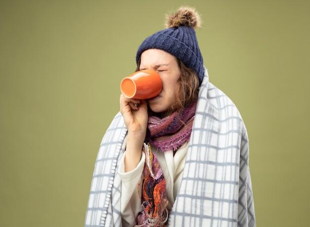 Niezadowolona młoda chora dziewczyna ubrana w białą szatę i czapkę zimową z szalikiem zawiniętą w kratę pije herbatę na oliwkowej zieleni
