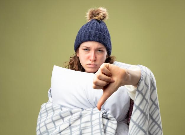 Niezadowolona młoda chora dziewczyna ubrana w biały szlafrok i czapkę zimową z szalikiem owiniętym w kratę przytuliła poduszkę pokazując kciuk w dół