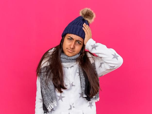 Niezadowolona młoda chora dziewczyna w czapce zimowej z szalikiem kładąc rękę na bolącej głowie na różowym tle