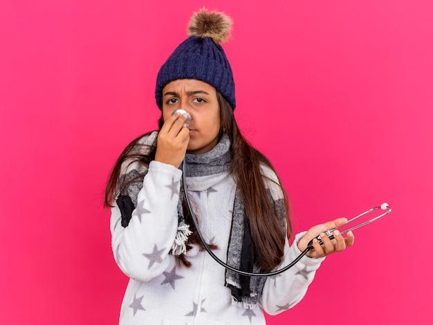 Niezadowolona młoda chora dziewczyna w czapce zimowej z szalikiem trzyma i stawia stetoskop na nosie na różowym tle