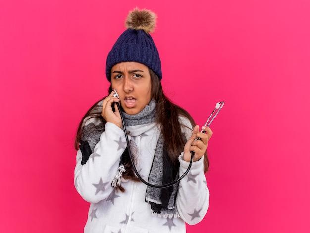 Niezadowolona młoda chora dziewczyna w czapce zimowej z szalikiem trzymając i stawiając stetoskop na policzku na różowym tle