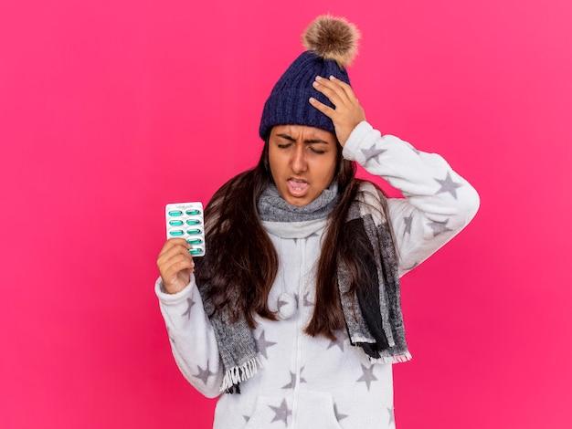 Niezadowolona młoda chora dziewczyna w czapce zimowej z szalikiem trzymając pigułki i kładąc rękę na bolącej głowie na różowym tle
