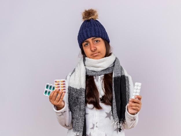 Niezadowolona młoda chora dziewczyna w czapce zimowej z szalikiem trzymając pigułki na białym tle