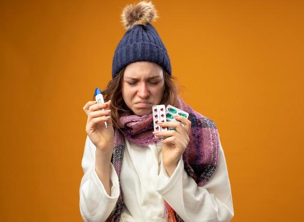 Niezadowolona młoda chora dziewczyna z zamkniętymi oczami w białej szacie i czapce zimowej z szalikiem trzymająca termometr z pigułkami odizolowanymi na pomarańczowej ścianie