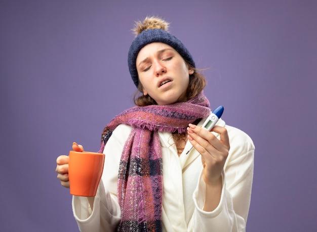 Niezadowolona młoda chora dziewczyna z zamkniętymi oczami w białej szacie i czapce zimowej z szalikiem trzymającym filiżankę herbaty i termometr na fioletowym tle