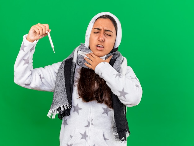 Niezadowolona młoda chora dziewczyna z zamkniętymi oczami zakładająca kaptur w szaliku trzymająca termometr kładąca dłoń na bolącym gardle na białym tle na zielonym tle