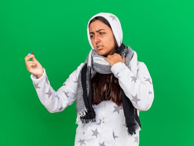 Niezadowolona młoda chora dziewczyna zakładająca kaptur na sobie szalik trzymając i patrząc na pigułki na białym tle na zielonym tle