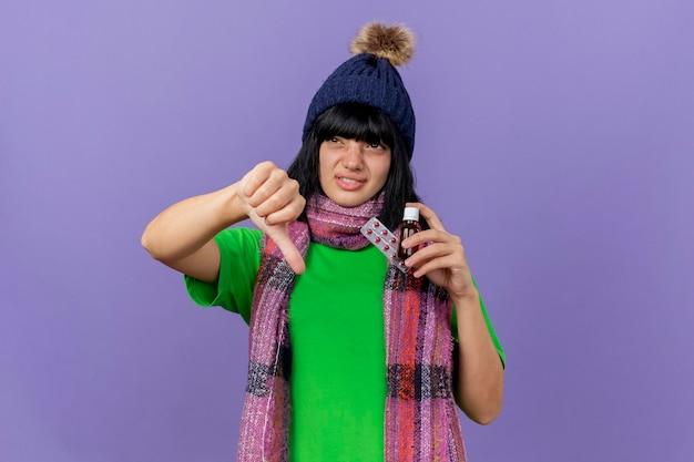 Niezadowolona młoda chora dziewczynka kaukaska w czapce zimowej i szaliku trzymająca lekarstwo w szkle i paczce kapsułek patrząc z boku, pokazując kciuk w dół odizolowany na fioletowym tle z miejscem na kopię