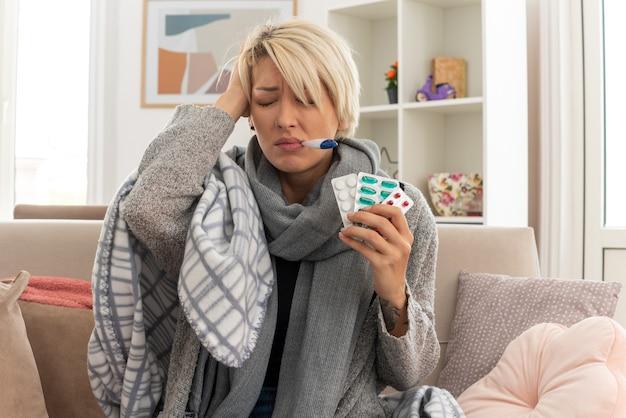 Niezadowolona młoda, chora słowiańska kobieta z szalikiem na szyi owinięta w kratę, mierząca jej temperaturę termometrem i trzymająca blistry z lekarstwami, siedząca na kanapie w salonie