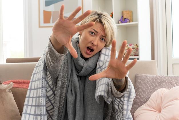Niezadowolona młoda, chora słowiańska kobieta z szalikiem na szyi owinięta w kratę wyciągając ręce siedząc na kanapie w salonie