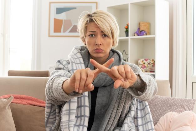 Niezadowolona młoda, chora słowiańska kobieta z szalikiem na szyi owiniętym w kratę krzyżującą palce, gestykulującą bez znaku, siedzącą na kanapie w salonie