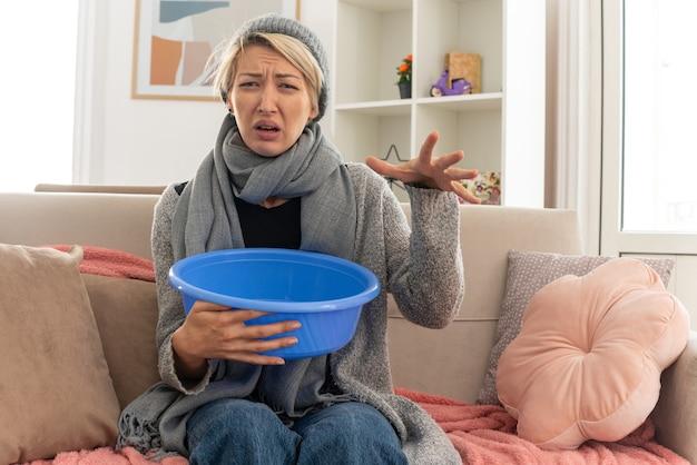 Niezadowolona młoda, chora słowiańska kobieta z szalikiem na szyi w czapce zimowej trzymająca wiadro i trzymająca rękę otwartą, siedzącą na kanapie w salonie