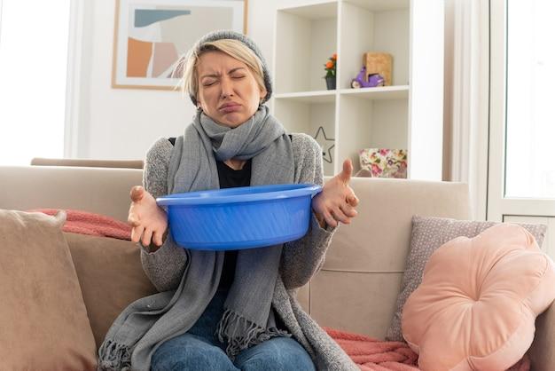 Niezadowolona młoda, chora słowiańska kobieta z szalikiem na szyi, w czapce zimowej, trzymająca wiadro, siedząca na kanapie z zamkniętymi oczami w salonie